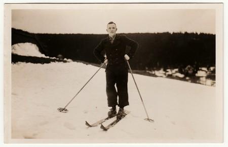 THE CZECHOSLOVAK REPUBLIC - CIRCA 1920s: Vintage photo shows man stays on skis in the winter mountains.  Antique black & white studio portrait. Редакционное