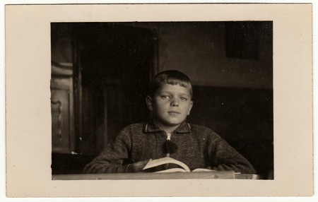 EILENBURG, GERMANY - CIRCA 1950s: Vintage photo shows pupil boy with book at the desk. Black & white retro photo.