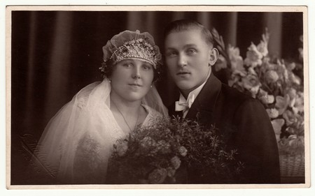 CHRASTAVA (KRATZAU), THE CZECHOSLOVAK  REPUBLIC - CIRCA 1930s: Vintage photo of newlyweds. Bride wears a veil and diadem. Black & white antique studio portrait.