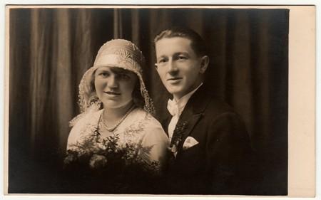 LIBEREC (REICHENBERG), THE CZECHOSLOVAK  REPUBLIC - CIRCA 1920s: Vintage photo of newlyweds. Bride wears white hat with lace (bobbin). Groom wears posh clothing, white bow-tie.  Black & white antique studio portrait. Editorial