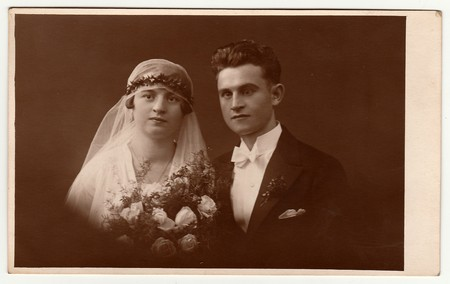 LIBEREC (REICHENBERG), THE CZECHOSLOVAK  REPUBLIC - CIRCA 1920s: Vintage photo of newlyweds with wedding bouquet. Bride wears wedding veil headdress. Groom wears posh clothing, white bow-tie. Black & white antique studio portrait. Editorial