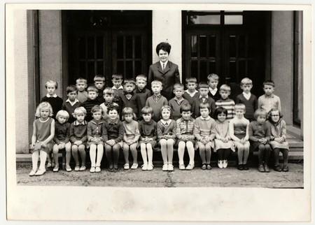 THE CZECHOSLOVAK SOCIALIST REPUBLIC - 1968: Vintage photo shows pupils (schoolmates) pose in front of school. Black & white antique photo. Editorial