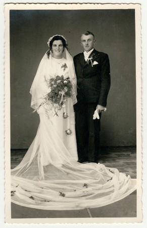 CESKY DUB, LA REPUBBLICA CECOSLOVACCA - CIRCA 1940: foto d'epoca degli sposi. La sposa indossa il velo, abito da sposa lungo e detiene il bouquet da sposa. Lo sposo indossa abito nero e papillon bianco. Ritratto in studio bianco e nero antico. Archivio Fotografico - 83512343