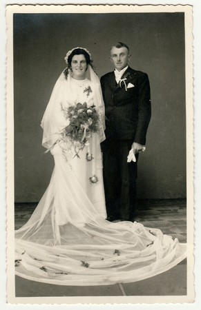 CESKY DUB, THE CZECHOSLOVAK  REPUBLIC - CIRCA 1940s: Vintage photo of newlyweds. Bride wears veil, long wedding gown and holds wedding bouquet. Groom wears black suit and white bow tie. Black & white antique studio portrait. Редакционное