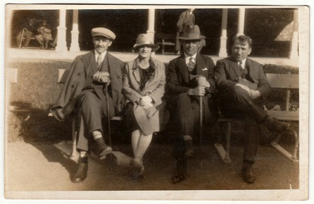 LUHACOVICE, THE CZECHOSLOVAK REPUBLIC - CIRCA 1940s: Vintage photo shows men and woman sit on a bench in spa resort. Black & white antique photography.