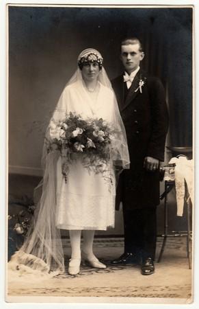 CHRASTAVA (KRATZAU), THE CZECHOSLOVAK  REPUBLIC - CIRCA 1930s: Vintage photo of newlyweds. Bride wears a long veil and holds wedding bouquet. Groom wears black suit and white bow tie. Black & white antique studio portrait.