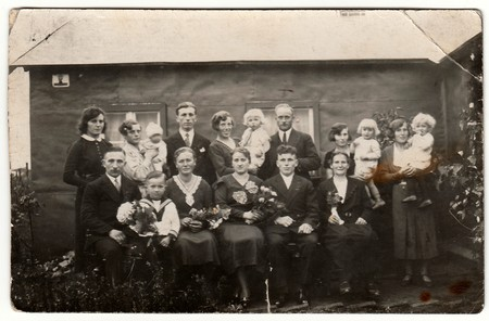 GERMANY - CIRCA 1940s: Vintage photo shows a big family poses behind house.  Black & white antique photography.