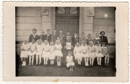 THE CZECHOSLOVAK REPUBLIC - CIRCA 1940s: Vintage photo of children at the First Communion. On photography is a priest and female teacher (schoolmistress). Éditoriale
