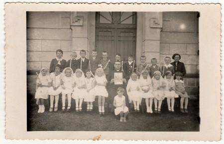 LA RÉPUBLIQUE TCHÉCOSLOVAQUE - CIRCA 1940: Photo vintage des enfants à la première communion. Sur la photographie est un prêtre et une enseignante (maîtresse d'école).