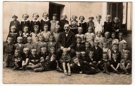 THE CZECHOSLOVAK REPUBLIC - SEPTEMBER 30, 1939: Vintage photo shows pupils (schoolmates) and their teacher pose in front of school. Black & white antique photography.