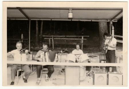 THE CZECHOSLOVAK SOCIALIST REPUBLIC - CIRCA 1970s: Retro photo shows musicians play during rural celebration. Black & white vintage photography.