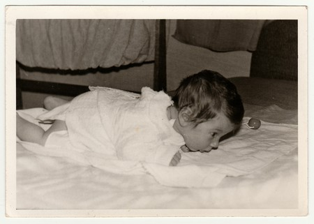 THE CZECHOSLOVAK SOCIALIST REPUBLIC - CIRCA 1970s: Retro photo shows cute baby crawls. Black & white vintage photography.