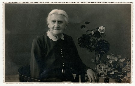 GERMANY - CIRCA 1930s: Vintage photo shows elderly woman sits on the period armchair in a photography studio. On the table are flowers. Retro black & white studio photography with sepia effect. Editorial