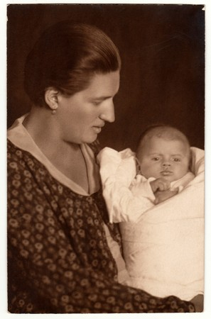 swaddling: THE CZECHOSLOVAK REPUBLIC - CIRCA 1930s: Vintage photo shows woman with baby (newborn) in swaddling clothes. Retro black & white studio photography.