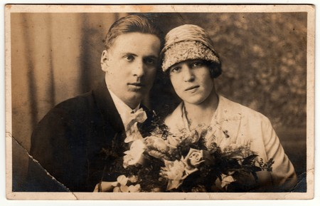 historical events: THE CZECHOSLOVAK REPUBLIC - CIRCA 1930s: Vintage photo shows newlyweds. Wedding ceremony - bride and groom. Bride holds wedding flowers. Retro black & white photography.