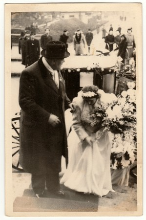 THE CZECHOSLOVAK REPUBLIC - CIRCA 1940s: Vintage photo shows a groom (bridegroom) and bride. A historical carriage (coach) is on the background. Retro black & white photography.