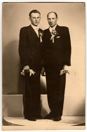 ZLIN, THE CZECHOSLOVAK REPUBLIC - CIRCA 1920s: Vintage photo shows two men (groom and his best man) pose in photography studio. Retro black & white photography.