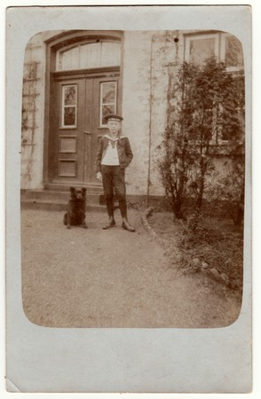 reich: HAMBURG, GERMANY (DEUTSCHES REICH) - CIRCA 1920s: Vintage photo shows boy poses in front of house. Boy wears a sailor costume and stands next to dog. Retro black & white photography. Editorial