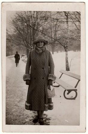 REPÚBLICA CHECA - CIRCA 1940: Foto de época muestra a una mujer en un invierno. La mujer lleva un abrigo largo con ribete de piel. Fotografía retro en blanco y negro. Foto de archivo - 83513033