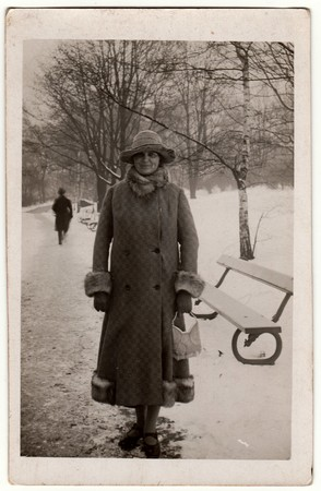 THE CZECHOSLOVAK REPUBLIC - CIRCA 1940s: Vintage photo shows woman in a winter time. Woman wears a long coat with fur bordering.  Retro black & white photography.