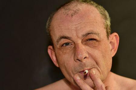 Man smokes cigarette on black background. Old man smokes. Real photo.