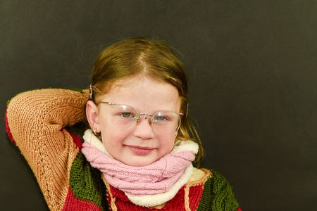 Portrait of attractive caucasian little girl with eyeglasses. Funny cute smiling child looking at camera on black background.