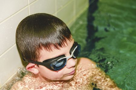 Boy in the indoor public pool. Portrait of child with swimmng goggles.