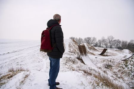 Middle age man standing in beautiful winter landscape . Man viewing on abandoned freestyle motocross ramps Stock Photo