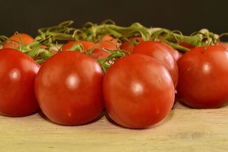 Fresh cherry tomatoes on rustic wooden background. White and black background Stock Photo