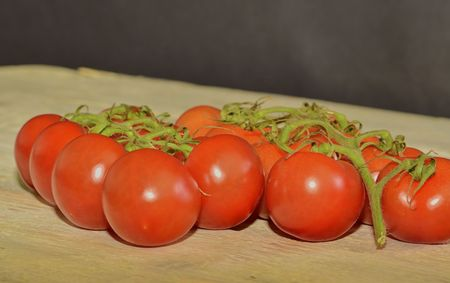 Fresh cherry tomatoes on rustic wooden background. White and black background. Copy space for text