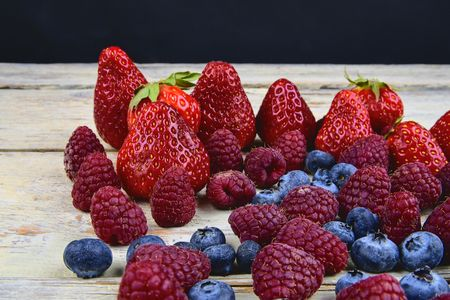 Healthy mixed fruit and ingredients with strawberry, raspberry, blueberry. Berries on rustic white wooden background.