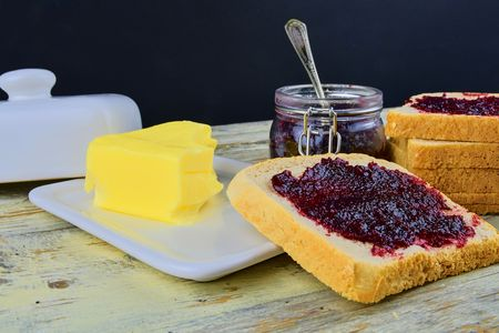 Jam, butter in butter dish and jam spread on toast.  Healthy and diet concept. Rural white wooden background. Stock Photo