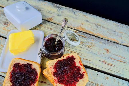 Jam, butter in butter dish and jam spread on toast.  Healthy and diet concept. Rural white wooden background. Flat design, top view. Stock Photo