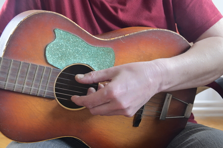 The hand of man playing guitar. Closeup. Musical concept