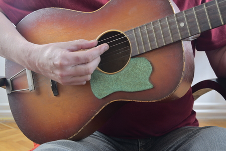 Male hand playing on acoustic guitar. Close-up. Musical concept Stock Photo