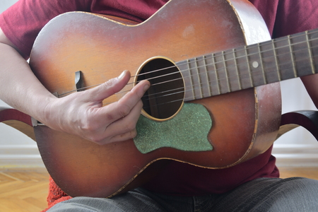 Closeup of mans hands playing acoustic guitar. Musical concept.