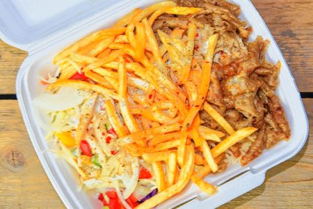 Fast food: kebabs, fries and fresh salad in the tray on the table. Unhealthy food concept