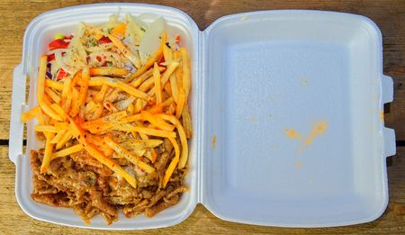Lunch Box: kebabs, fries and fresh salad in tray. Close-up on the table. Unhealthy food concept