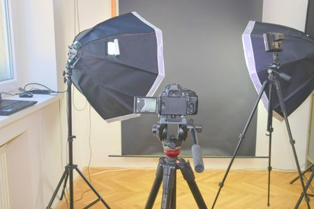 Empty photo studio with lighting equipment. Professional camera with picture of photo studio.