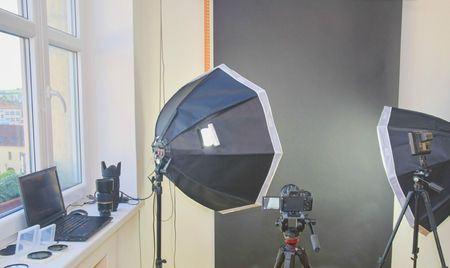 Empty photo studio with lighting equipment. Professional camera, lenses and filters for photographer.