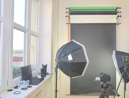 Empty photo studio with lighting equipment. Professional camera, lenses and filters for photographer