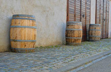 Old rustic wine barrels in front of modern wine cellar. Wine background in Europe. Czech Republic, South Moravia