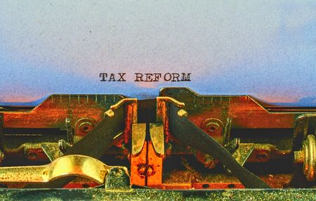 Closeup on vintage typewriter. Front focus on letters making TAX REFORM text. Business concept image with retro office tool Banco de Imagens