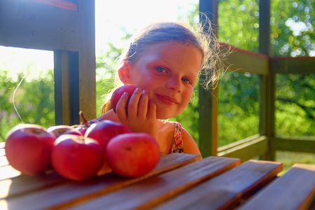 The little girl is sitting at a table on a verandah and eatting fresh apples. Apples on table. Dreamy and romantic image. Summer and happy childhood concept Foto de archivo
