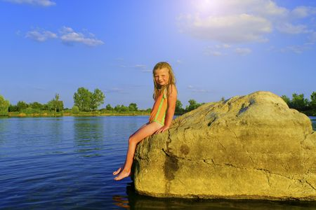 Cute little girl in a bathing suit sitting on a large rock by the lake at sunset. Summer and happy childhood concept. Copy space in bright blue sky Stock Photo