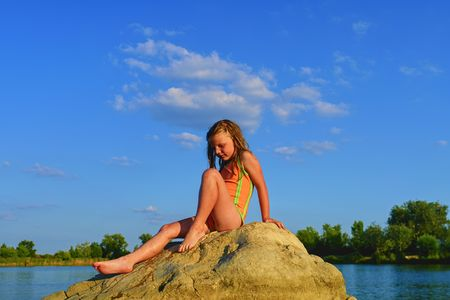 Portrait of child blond girl posing in swimsuit on rocks inside the lake. Summer and happy childhood concept. Copy space in bright blue sky