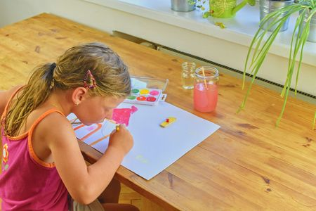 Cute little girl painting picture of house. Mortage concept. Selective focus, small DOF