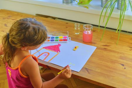 Little girl painting simple picture. Cute girl painting with watercolors. Window background. Selective focus and small DOF