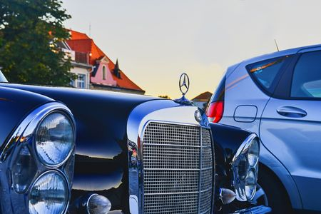 Mercedes Benz logo on a black vintage car.  Mercedes-Benz is a German automobile producer. The brand is used for luxury automobiles, buses, coaches and trucks.
