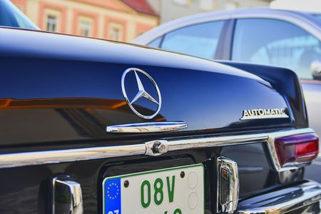 Mercedes Benz logo on a black vintage car. Close-up. Mercedes-Benz is a German automobile manufacturer. The brand is used for luxury automobiles, buses, coaches and trucks.